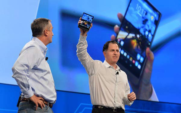 Michael Dell holds his skinny tablet aloft